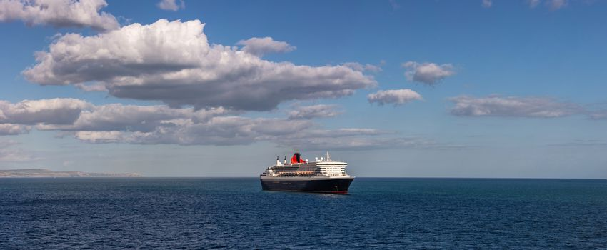 Weymouth Bay, United Kingdom - July 6, 2020: Beautiful panoramic shot of Cunard cruise ship Queen Mary 2 anchored in Weymouth Bay. Beautiful blue sky as a background.