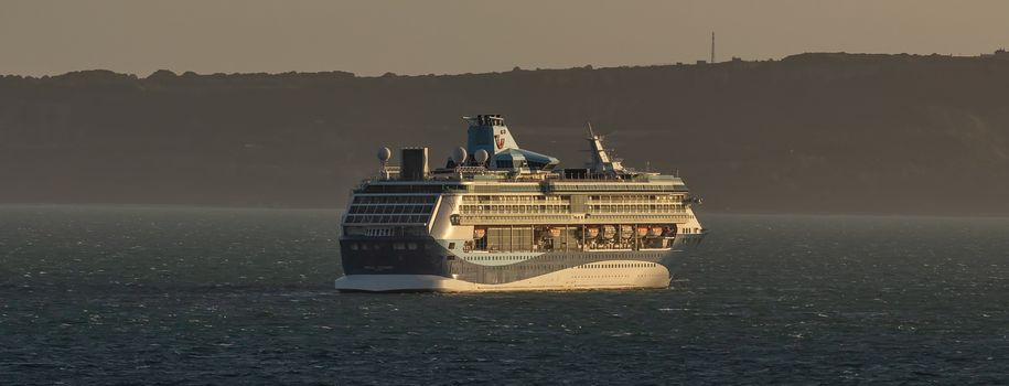 Weymouth Bay, United Kingdom - July 5, 2020: Beautiful shot of cruise ship Marella Discovery anchored in Weymouth Bay at sunset.