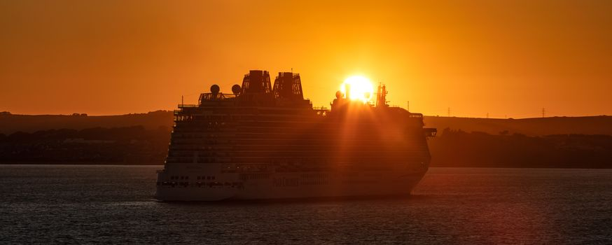 Weymouth Bay, United Kingdom - July 10, 2020: Amazing panoramic shot of P&O cruise ship Britannia anchored in Weymouth Bay at sunset. Sun setting down right above the ship casting orange color on it
