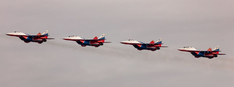 Barnaul, Russia - September 19, 2020: A low angle shot of Strizhi MiG-29 fighter jet squadron performing stunts during an aeroshow.