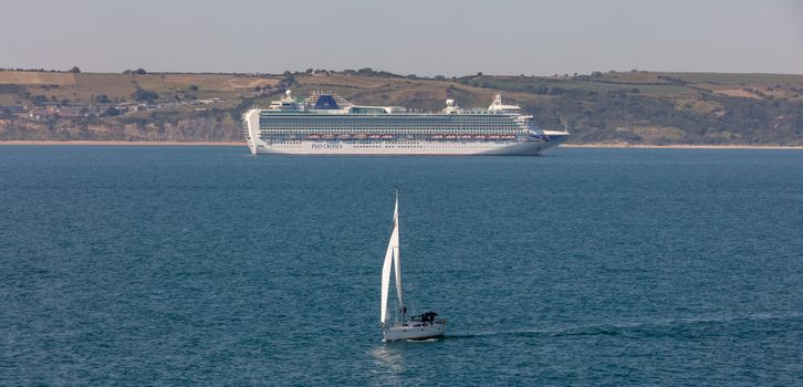 Weymouth Bay, United Kingdom - June 25, 2020: Beautiful panoramic shot of P&O cruise ship Ventura anchored in Weymouth Bay. Sail boat moving in the foreground.