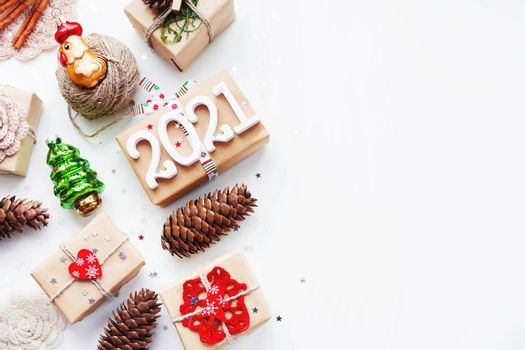 Christmas present on white background with copy space. New Year 2021 gifts wrapped in craft paper with decorations. Winter holiday symbols.