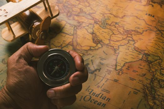 Hand hold old compass discovery and wooden plane on vintage pape