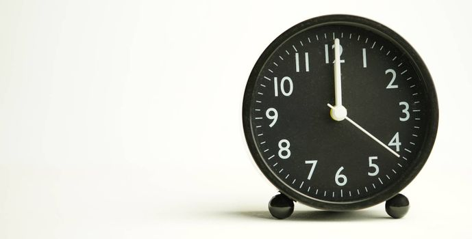 Decorative black alarm clock for noon separating white background with copy space.