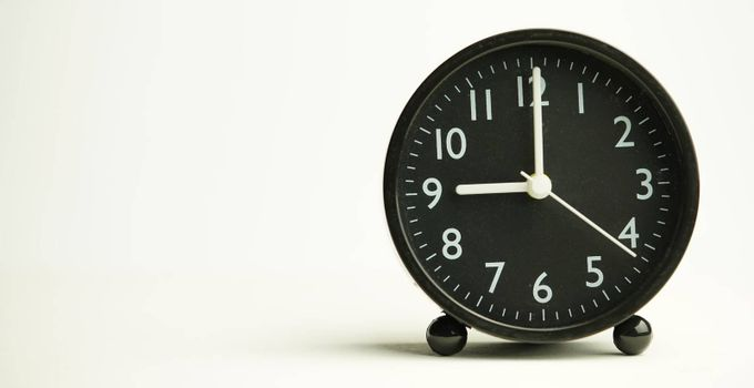 Decorative close-up black alarm clock at 9 o'clock isolated on white background with abstract copy space, start time of working day.