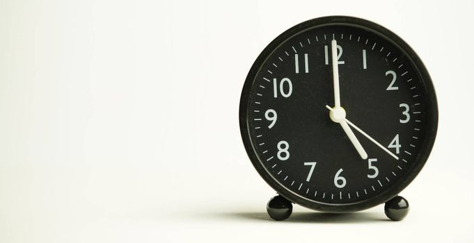 Decorative close-up black analog alarm clock for 5 o'clock or 17 o'clock, separate white background with copy space.