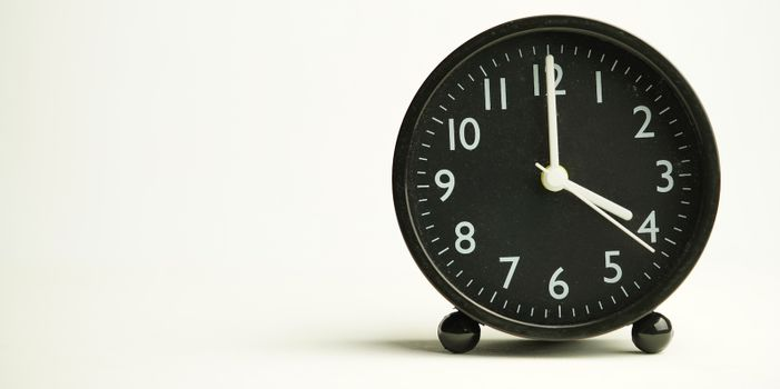 Decorative close-up black analog alarm clock for 4 or 16 o'clock, separate white background with copy space.