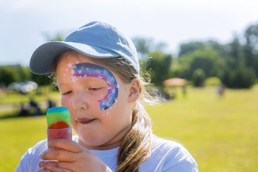Teenager with face paint eating rainbowl color ice cream.