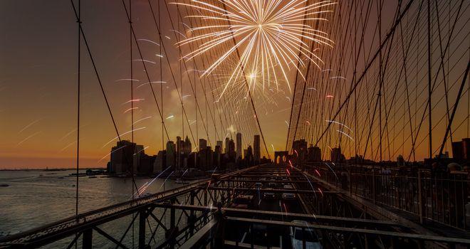 Festive fireworks on a brooklyn Bridge sunset with Manhattan skyline in New York