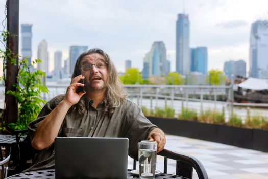 Panorama of downtown Manhattan man calling by the phone working in coffee shop on laptop computer