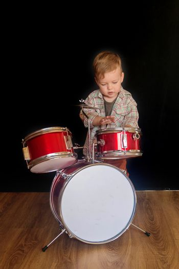 Two year caucasian boy is Playing Drum Set Isolated on Black Background