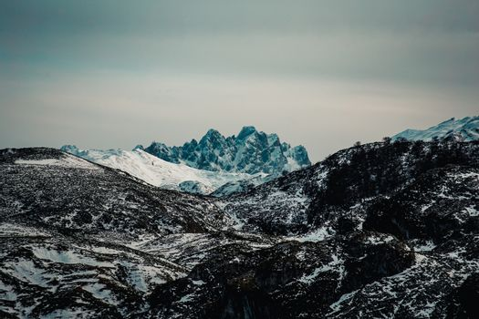 Massive and risky peak in the mountain range during winter