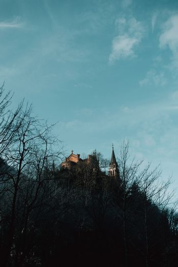 Medieval castle on the top of a hill with tree silhouettes and a clear sky with copy space covadonga