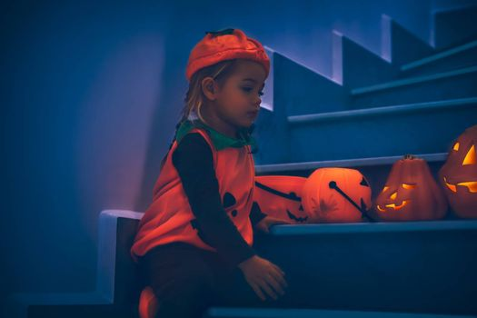 Cute Baby Sitting on the Stairs and Decorating Home with Beautiful Carved Pumpkins. Jack o Lanterns. Dressed Like a Small Festive Pumpkin. Happy Autumnal Holidays