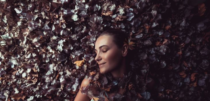 Profile Fashion Portrait of a Beautiful Gentle Girl Lying Down in the Pile of Dry Tree Leaves and Flowers. Seasonal Change. Authentic Beauty of Autumn.