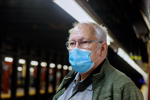 Safety in a public place while epidemic mature man wearing disposable medical face mask of the subway in New York during coronavirus outbreak of covid-19.