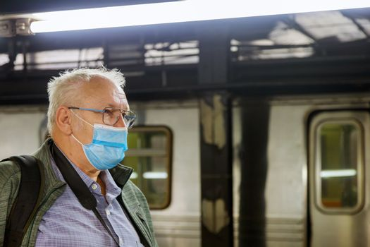 Man in face disposable mask in the Covid-19 subway station coronavirus epidemic pandemic on train metro tube male health care.