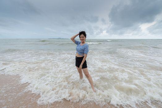 Asian beautiful girl has felt happy on the beach with a cloudy sky.