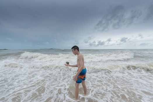 An Asian boy has to hold a stone on the beach with a cloudy sky.