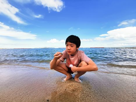 An Asian boy has playing a stone on the beach with blue sky in the morning.