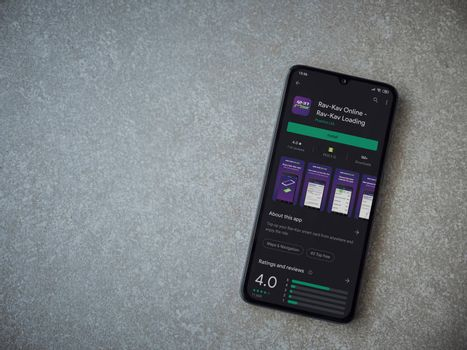 Lod, Israel - July 8, 2020: Rav Kav Online app play store page on the display of a black mobile smartphone on ceramic stone background. Top view flat lay with copy space.