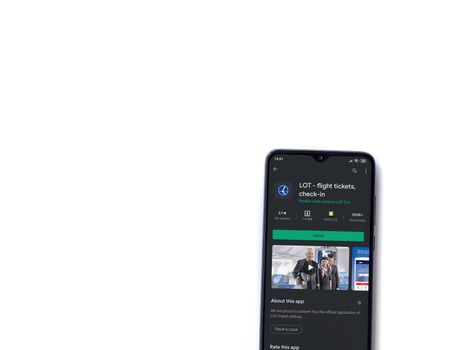 Lod, Israel - July 8, 2020: LOT app play store page on the display of a black mobile smartphone isolated on white background. Top view flat lay with copy space.