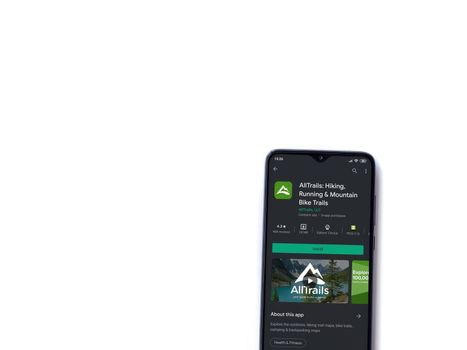 Lod, Israel - July 8, 2020: AllTrails app play store page on the display of a black mobile smartphone isolated on white background. Top view flat lay with copy space.