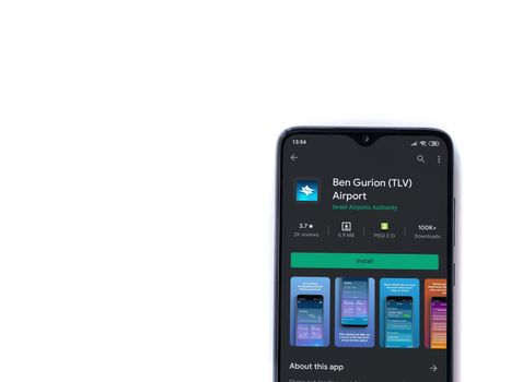 Lod, Israel - July 8, 2020: Ben Gurion Airport app play store page on the display of a black mobile smartphone isolated on white background. Top view flat lay with copy space.