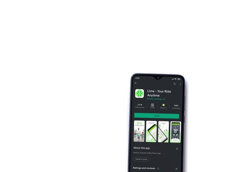 Lod, Israel - July 8, 2020: Lime app play store page on the display of a black mobile smartphone isolated on white background. Top view flat lay with copy space.