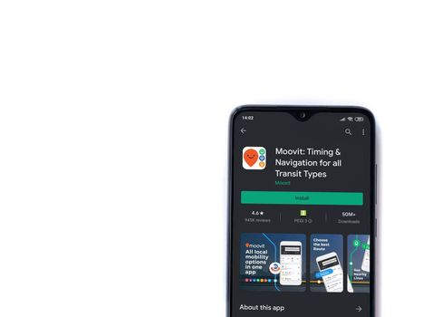 Lod, Israel - July 8, 2020: Moovit app play store page on the display of a black mobile smartphone isolated on white background. Top view flat lay with copy space.