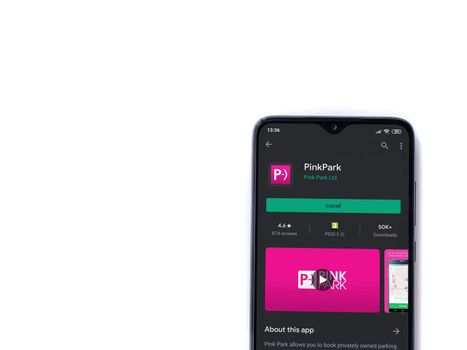 Lod, Israel - July 8, 2020: Pink Park app play store page on the display of a black mobile smartphone isolated on white background. Top view flat lay with copy space.