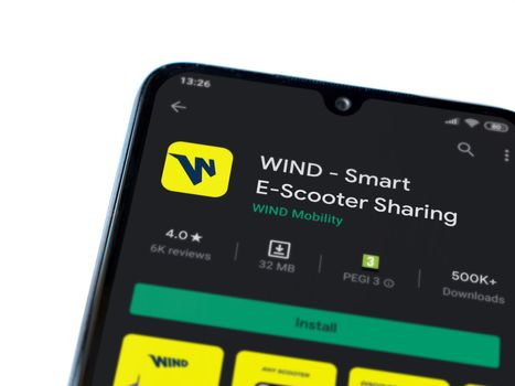 Lod, Israel - July 8, 2020: WIND app play store page on the display of a black mobile smartphone isolated on white background. Top view flat lay with copy space.