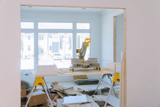 Construction remodeling home cutting wooden trim molding on with circular saw.