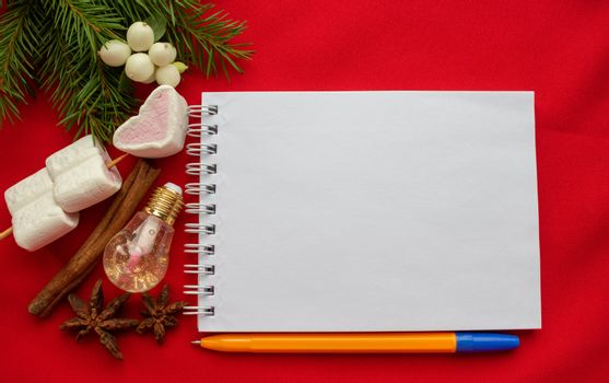 Christmas composition. Notepad and pen, spruce branches, marshmallow hearts,white dogwood berries,cinnamon stick on a red background. Christmas, winter, New year