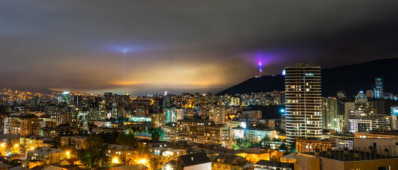 Dramatic night sky with  light of Moon through the clouds over Tbilisi's downtown, capital city of Georgia