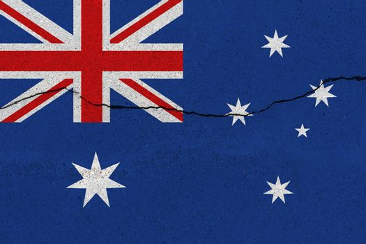 Australia flag on concrete wall with crack. Patriotic grunge background. National flag of Australia