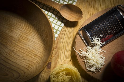 Wooden utensils and metal grater with ingredients for making pasta