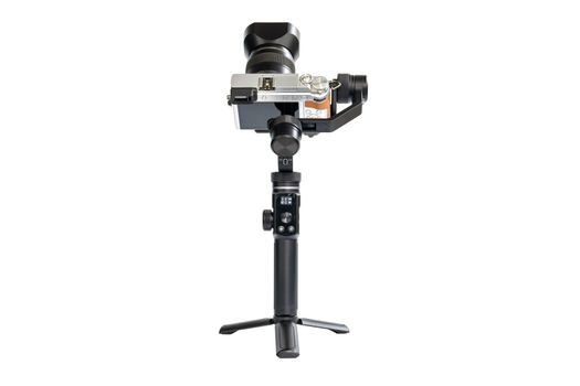 DSLR camera is mounted on a 3-axis motor stabilizer for smooth video recording isolated on white background.