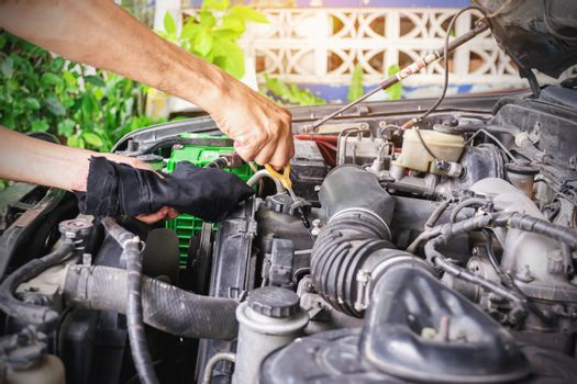 Cars mechanic is checking the level of engine oil from the engine oil level gauge of the car, Automotive industry and garage concepts.