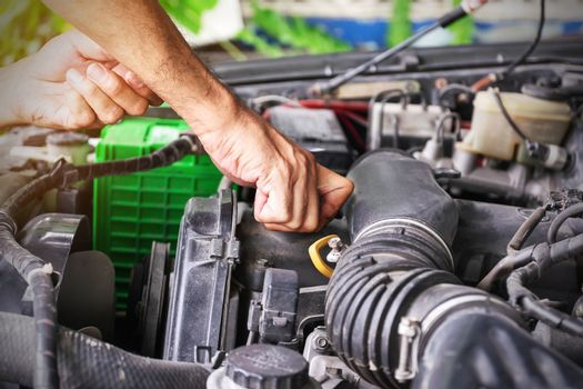 Cars mechanic is closing the engine oil lid after adding the oil to the engine to the level, Automotive industry and garage concepts.