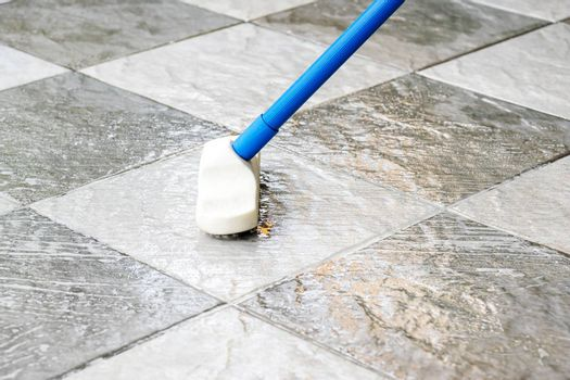 Clean the tile floor with a long-handled floor brush.