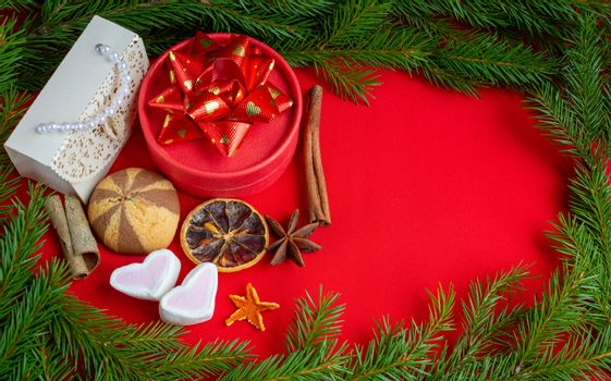 Christmas gifts lie on the background of a spruce branch on a red background. Copy of the space, banner.
