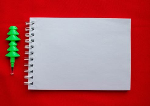 Christmas composition Notepad and pen in the form of a Christmas tree on a red background.The concept of Christmas.