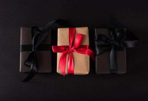 Black Friday Sale shopping concept, Top view of gift box wrapped black paper and black bow ribbon present around the brown box with red bow ribbon, studio shot on dark background