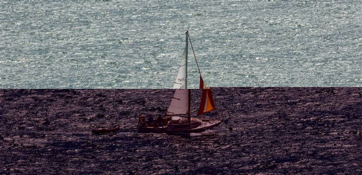 Portland Harbor, UK - July 2, 2020: White sailboat sailing in the harbor. Small rescue boat tagging along.