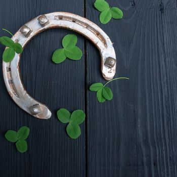 clover leaves and golden horseshoe on vintage wooden boards, selective focus. Good luck symbol, St. Patrick's Day and New Year concept.