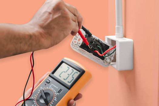 Electrician is using a digital meter to measure the voltage at the power outlet  isolated on orange color pastel background, with clipping path.