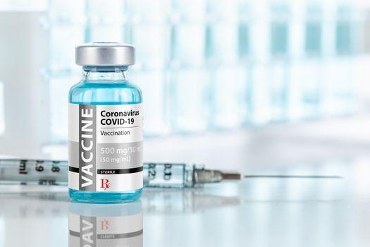 Coronavirus COVID-19 Vaccine Vial and Syringes On Reflective Surface Near Test Tubes.