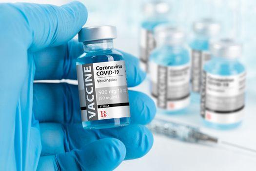 Doctor or Nurse Wearing Surgical Glove Holding Coronavirus COVID-19 Vaccine Vial.