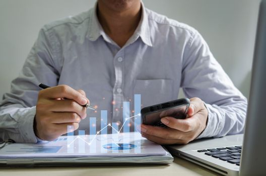 Businessman report graphs and charts of financial statements and profit growth holding a pen and mobile phone at desk.Business concept of digital communication technology